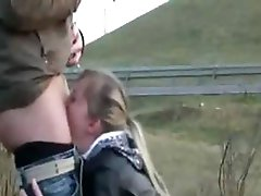 Blond is on her knees sucking his cock on the side of the road