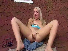 A blonde teenage girl is on top of a roof where she slowly takes her...